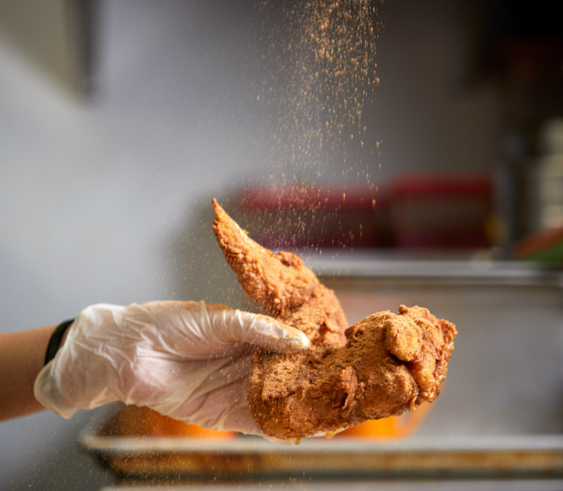 Person ssprinkling spices on a piece of chickeen